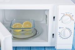 Um forno micro-ondas branco novo, em uma superfície de madeira azul para aquecer-se Imagens de Stock