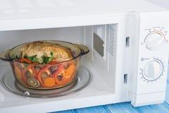 Um forno micro-ondas branco novo, em uma superfície de madeira azul para aquecer-se Foto de Stock
