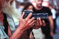 Um fotógrafo com uma barba que guarda uma câmera Imagens de Stock
