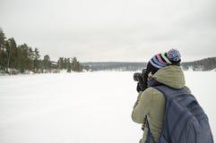 Um fotógrafo da mulher na roupa morna guarda uma câmera em suas mãos e toma imagens da paisagem do inverno Contra o contexto imagem de stock