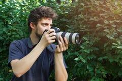 Um fotógrafo do retrato que tome a foto No fundo de arbustos verdes imagem de stock