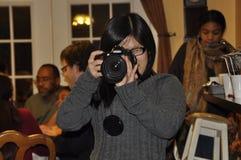 Um fotógrafo fêmea toma imagens durante um evento imagens de stock