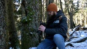 Um fotógrafo masculino farpado do viajante com sua câmera na floresta do inverno toma imagens da natureza Conceito do curso para video estoque
