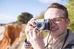 Um fotógrafo que toma imagens dos penhascos e do oceano durante ensolarado imagens de stock royalty free