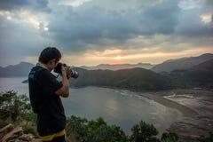 Um fotógrafo toma a foto na zona intertidal Imagem de Stock