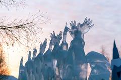 Um fragmento de um gelo que escultura-muitas mãos aumentaram para o céu fotos de stock royalty free