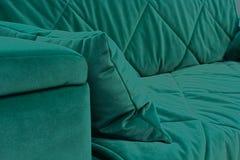 Um fragmento de um sofá verde de veludo fotografia de stock