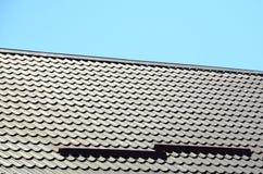 Um fragmento de um telhado de uma telha do metal da obscuridade - cor vermelha Qualit Fotos de Stock