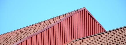 Um fragmento de um telhado de uma telha do metal da obscuridade - cor vermelha Qualit Fotos de Stock Royalty Free