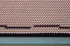 Um fragmento de um telhado de uma telha do metal da obscuridade - cor vermelha Qualit Foto de Stock