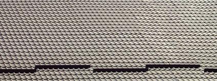 Um fragmento de um telhado de uma telha do metal da obscuridade - cor vermelha Qualit Imagens de Stock Royalty Free