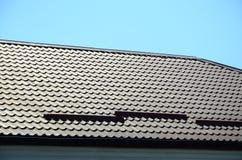 Um fragmento de um telhado de uma telha do metal da obscuridade - cor vermelha Qualit Imagem de Stock Royalty Free