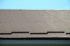 Um fragmento de um telhado de uma telha do metal da obscuridade - cor vermelha Qualit Imagem de Stock