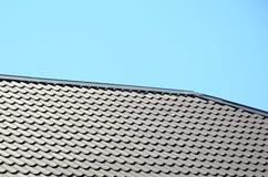 Um fragmento de um telhado de uma telha do metal da obscuridade - cor vermelha Qualit Imagens de Stock