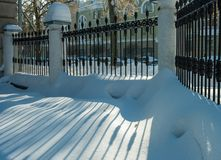 Um fragmento de uma cerca preta do ferro forjado com um teste padrão na neve Dia de inverno imagens de stock royalty free