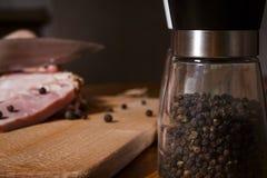 Um frasco com pimenta preta no fundo de uma carne Foto de Stock Royalty Free