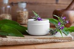 Um frasco da pomada caseiro da raiz da consolda-maior com comf de florescência fresco fotos de stock