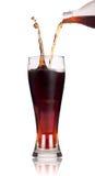 Um frasco da soda da cola que derrama em um vidro Imagem de Stock Royalty Free