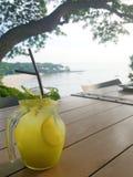 Um frasco de vidro da limonada congelada da soda é lugar na tabela de madeira com opinião do mar Imagens de Stock