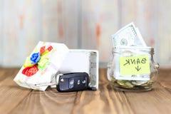 um frasco de vidro em sua moeda, um carro do brinquedo, uma caixa de presente O conceito faz um depósito no banco e ganha um carr fotos de stock royalty free