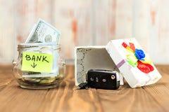 um frasco de vidro em sua moeda, um carro do brinquedo, uma caixa de presente O conceito faz um depósito no banco e ganha um carr imagem de stock