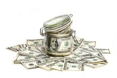 Um frasco de vidro encheu-se com os dólares entre cem notas de dólar em um fundo branco Imagem de Stock