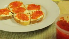 Um frasco do caviar vermelho e de uma placa branca com canapes com manteiga e cavia vídeos de arquivo