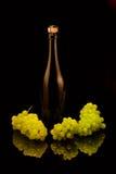 Um frasco do champanhe e das uvas Foto de Stock Royalty Free