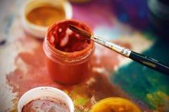 Um frasco do guache vermelho e uma escova estão na paleta fotografia de stock royalty free