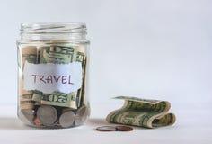 Um frasco encheu-se com as moedas e as notas de dólar dos E.U. Imagens de Stock