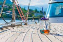 Um frasco transparente com uma bebida agradável está na plataforma do iate Foto de Stock