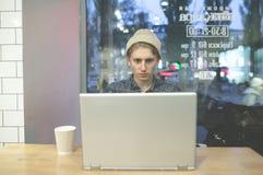 Um freelancer novo à moda trabalha em um café acolhedor para um portátil O moderno usa um computador em um café para uma xícara d Fotografia de Stock Royalty Free