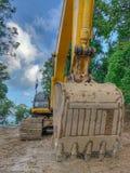 Um funcionamento da escavadora da máquina escavadora no local da construção de estradas fotografia de stock royalty free