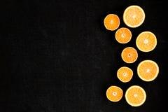 Um fundo preto da madeira compensada na composição com corte nas laranjas e nas tangerinas das metades colocadas no semicírculo Imagens de Stock Royalty Free