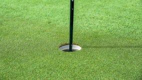 Um furo da bola de golfe no campo de golfe imagens de stock