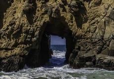 Um furo em um pico rochoso no oceano fotografia de stock royalty free