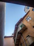 Um furo no céu no telhado desmoronou na construção histórica velha com balcões, janelas e portas de entrada nas ruas de Imagem de Stock