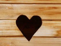 Um furo sob a forma de um coração cortou em um plano que consiste em placas secas Um símbolo do amor e do relacionamento Humor ro imagem de stock