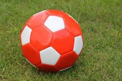 Um futebol vermelho na grama Fotos de Stock Royalty Free