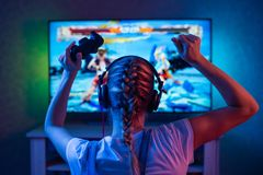 Um gamer ou uma menina da flâmula em casa em uma sala escura com um gamepad que joga com os amigos nas redes nos jogos de vídeo U foto de stock