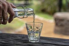 Um garçom em um restaurante derrama a água fresca de uma garrafa em um vidro, fim acima imagem de stock