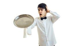 Um garçom novo em uma camisa branca esticou a bandeja dianteira do alimento e mantém a bola atrás da cabeça Foto de Stock Royalty Free