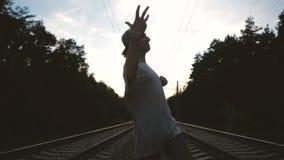 Um garoto dança krump, faz um movimento legal à mão perto da trilha ferroviária no pôr do sol, em câmera lenta filme