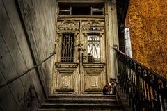 Um gatinho pequeno senta-se na entrada da porta de uma construção velha Fotografia de Stock