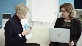 Um gerente fêmea apresenta o plano novo do projeto aos colegas no encontro, explicando ideias aos colegas de trabalho no escritór video estoque
