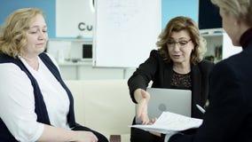 Um gerente fêmea apresenta o plano novo do projeto aos colegas no encontro, explicando ideias no flipchart aos colegas de trabalh filme