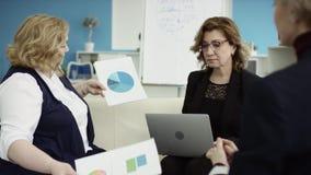Um gerente fêmea apresenta o plano novo do projeto no encontro, explicando ideias no flipchart aos colegas de trabalho no escritó vídeos de arquivo