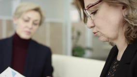 Um gerente f?mea apresenta o plano novo do projeto aos colegas no encontro, explicando ideias no flipchart aos colegas de trabalh vídeos de arquivo