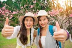 Um gesto à moda de duas meninas entrega o polegar acima fotos de stock