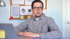 Um gestor de escritório do homem novo que olha à câmera que senta-se em seu local de trabalho video estoque